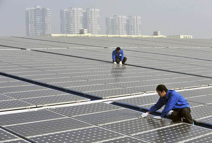 Technicians maintain solar panels on a roof at a solar power plant in Wuhan // SolarPV.TV